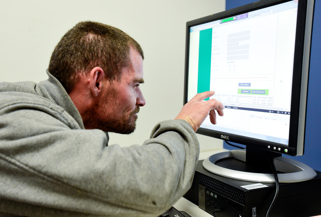 . Glenn Tefft checks out fine print while filling out a job application at the Longmont Library computer lab on Tuesday.  Matthew Jonas/Staff Photographer April 4,  2017