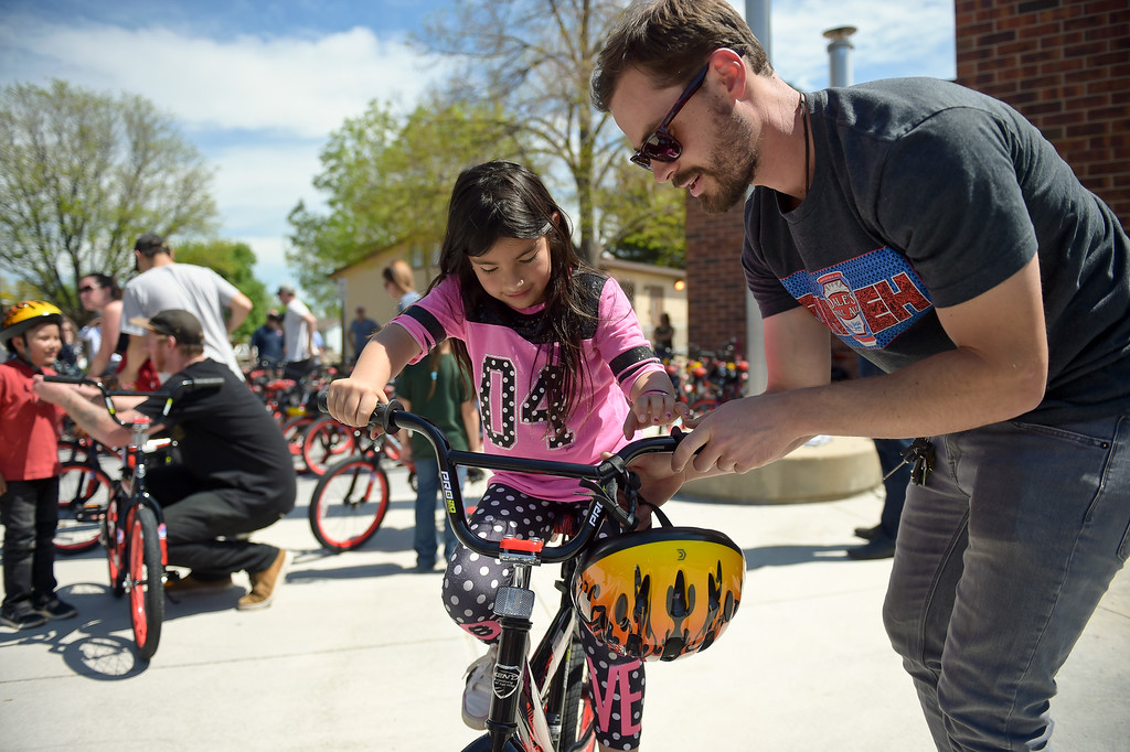 . Oskar Blues\' Thomas Appel helps first grader Brianna Avila-Sotello with her new bike during the CAN\'d Aid Foundation\'s bike giveaway Tuesday afternoon at Indian Peaks Elementary, 1335 S. Judson St. To view more photos visit timescall.com. Lewis Geyer/Staff Photographer May 15, 2018