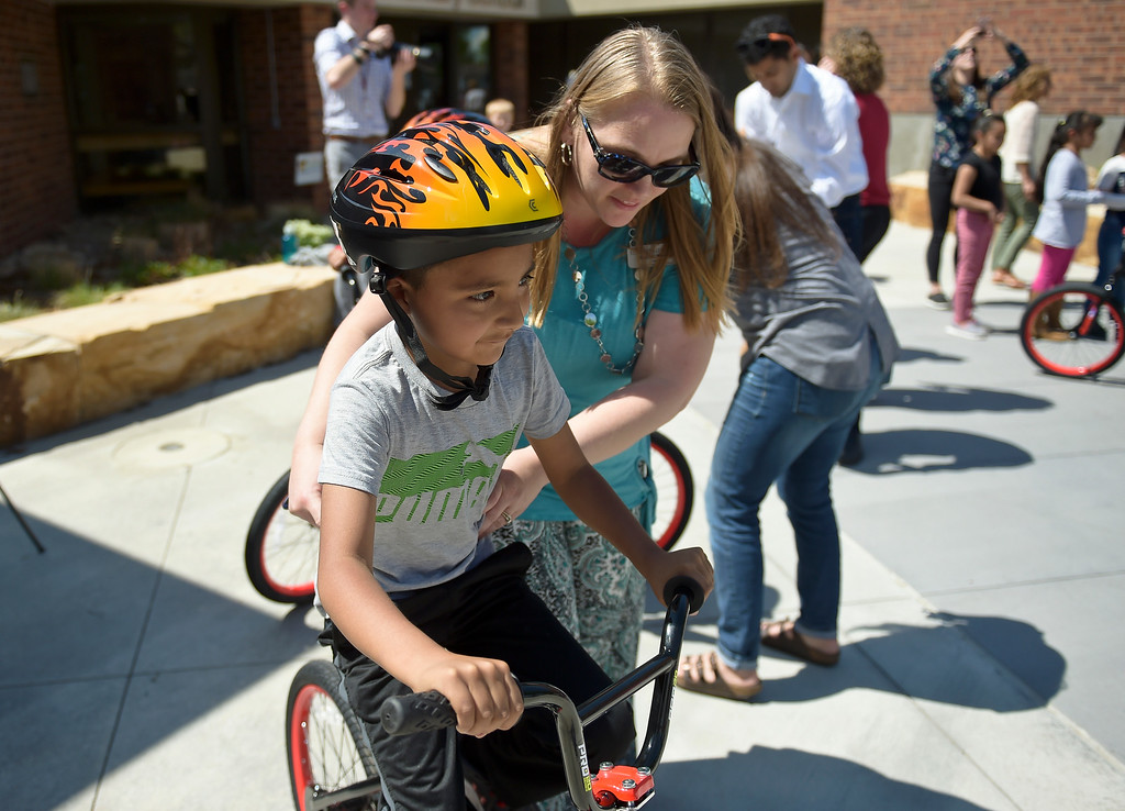 . First grader Yahir Guzman gets a little help from Mendi Young at the CAN\'d Aid Foundation\'s bike giveaway Tuesday afternoon at Indian Peaks Elementary, 1335 S. Judson St. To view more photos visit timescall.com. Lewis Geyer/Staff Photographer May 15, 2018