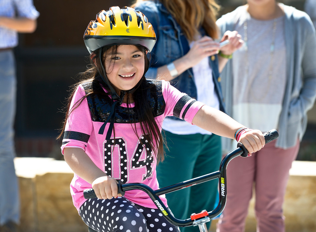 . First grader Brianna Avila-Sotello rides her new bike during the CAN\'d Aid Foundation\'s bike giveaway Tuesday afternoon at Indian Peaks Elementary, 1335 S. Judson St. To view more photos visit timescall.com. Lewis Geyer/Staff Photographer May 15, 2018