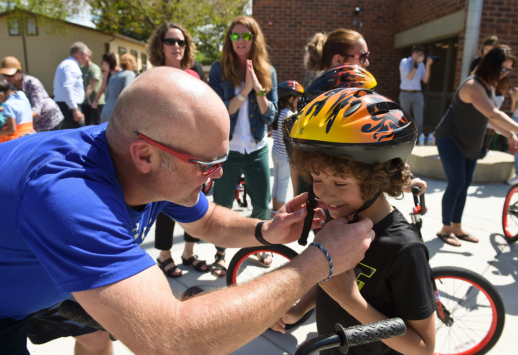 . Oskar Blues founder Dale Katechis helps second grader Antonio Gutierrez with his new helmet at the CAN\'d Aid Foundation\'s bike giveaway Tuesday afternoon at Indian Peaks Elementary, 1335 S. Judson St. To view more photos visit timescall.com. Lewis Geyer/Staff Photographer May 15, 2018