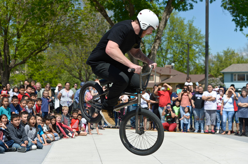 . Oskar Blues\' Mike Murfitt performs stunts during the CAN\'d Aid Foundation\'s bike giveaway Tuesday afternoon at Indian Peaks Elementary, 1335 S. Judson St. To view more photos visit timescall.com. Lewis Geyer/Staff Photographer May 15, 2018