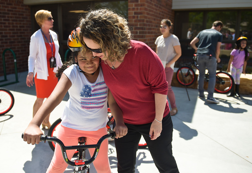 . First grader Marisa Davila gets a hug from literacy interventionist Lynn Helmstetter at the CAN\'d Aid Foundation\'s bike giveaway Tuesday afternoon at Indian Peaks Elementary, 1335 S. Judson St. To view more photos visit timescall.com. Lewis Geyer/Staff Photographer May 15, 2018