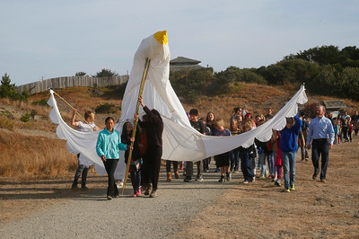 Redwood Coast Montessori students, carrying a giant peace dove, and teachers parade around the Manila Community grounds where their school is based on Friday morning, which was International Day of Peace. (Shaun Walker -- The Times-Standard)