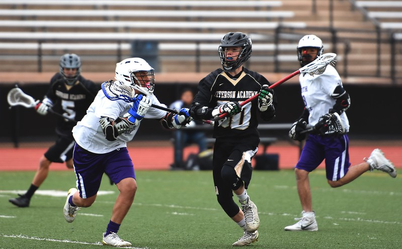 Jefferson Academy's Ethan Kupka pushes the ball down the field during the Jaguars' game against Denver North on Friday, April 13, at All-City Stadium in Denver.