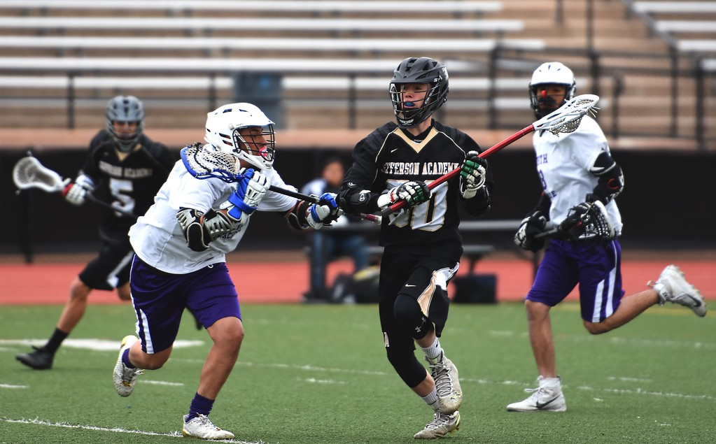 . Jefferson Academy\'s Ethan Kupka pushes the ball down the field during the Jaguars\' game against Denver North on Friday, April 13, at All-City Stadium in Denver.