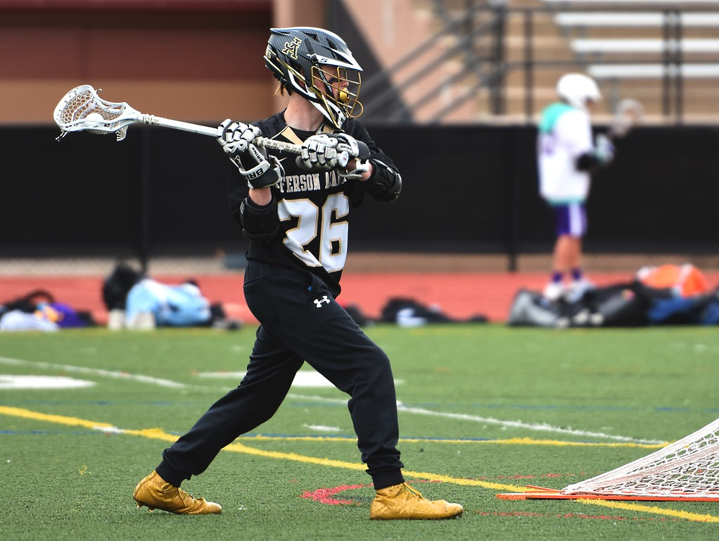 . Jefferson Academy\'s Ryan Reffel passes from behind the opposing team\'s goal during the Jaguars\' game against Denver North on Friday, April 13, at All-City Stadium in Denver.