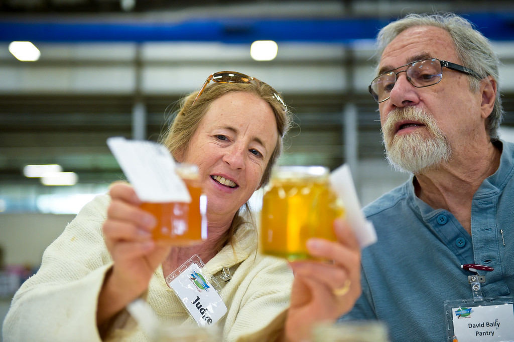 . Judge Ruth Widrick asks for assistance from supervisor David Bailey while Widrick judges honey during open judging in the Exhibit Building Thursday morning. To view more photos visit timescall.com. (Photo by Lewis Geyer/Staff Photographer) August 02, 2018