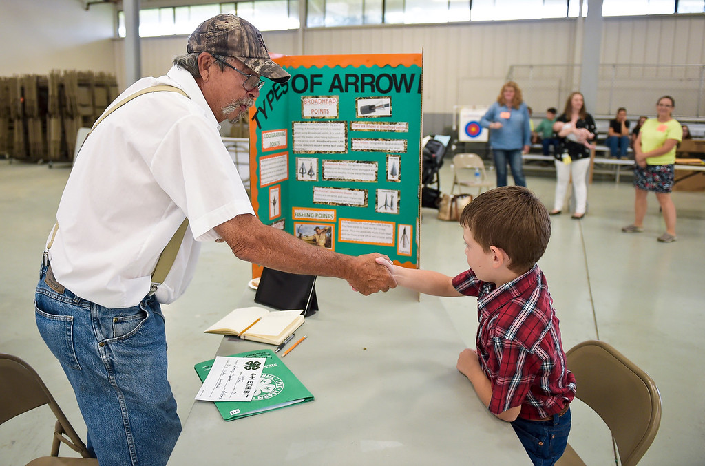 . Shooting sports judge Perry Brewer shakes hands with Cooper Cutter, 8, of Greeley, at the start of Cooper\'s  4-H archery interview in the Exhibit Building Thursday morning. Cutter is a member of the Rinn Valley 4-H Club. To view more photos visit timescall.com. (Photo by Lewis Geyer/Staff Photographer) August 02, 2018