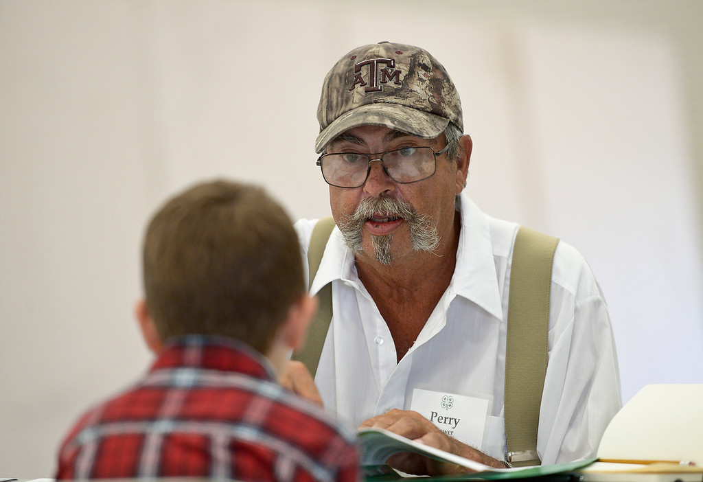 . Cooper Cutter, 8, of Greeley, is interviewed about his archery project by shooting sports judge Perry Brewer during 4-H interview judging in the Exhibit Building Thursday morning. Cooper is a member of the Rinn Valley 4-H Club. To view more photos visit timescall.com. (Photo by Lewis Geyer/Staff Photographer) August 02, 2018