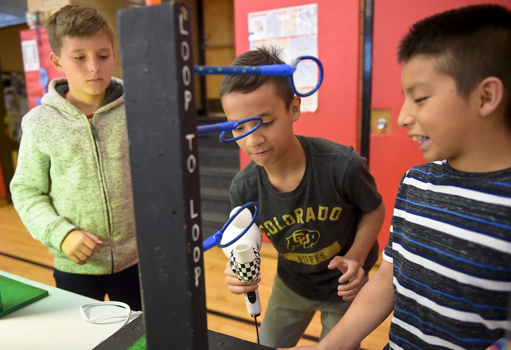 . Fourth graders Max McKinney, left, and Axel Moreno, right, watch classmate Emilio Manjarrez try his hand at using a hair dryer to blow a ping pong ball through hoops during CSU\'s Little Shop of Physics Thursday morning at Central Elementary, 1020 Fourth Ave. To view more photos and a video visit timescall.com. Lewis Geyer/Staff Photographer April 12, 2018