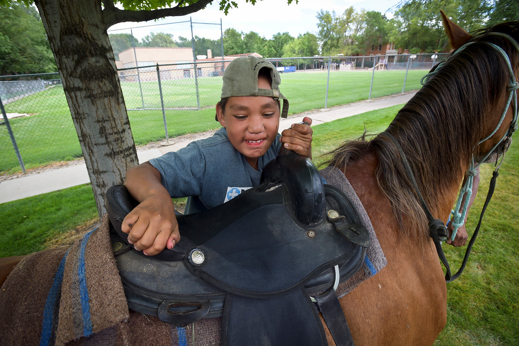 . Thomas Belt, 10, gets on a horse along Gay Street, behind Central Elementary, during a break in the Lakota Ride 2017 as it passed through Longmont Tuesday. The 400-mile ride, which started in Golden Saturday, raises money and awareness for families living on the Pine Ridge Reservation in South Dakota. It is expected to end at the reservation in mid August. To view more photos and a video visit timescall.com. Lewis Geyer/Staff Photographer July 25, 2017