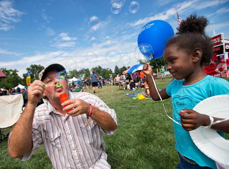 "Mark Tedford blows bubbles for his granddaughter during Leftapalooza in Roosevelt Park in Longmont on Saturday. Left Hand Brewing Company's event raised funds and support for the Leukemia & Lymphoma Society and the Left Hand Brewing Foundation.<br /> More photos:  <a href=""http://www.dailycamera.com"">http://www.dailycamera.com</a><br /> (Autumn Parry/Staff Photographer)<br /> August 6, 2016"