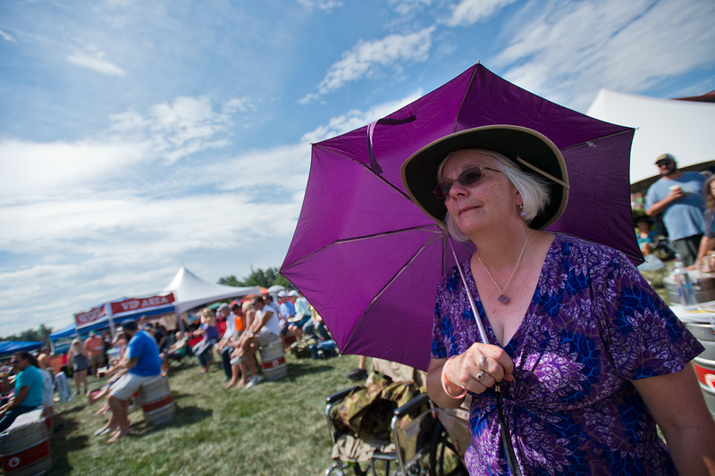 "Elaine Niesen shades herself from the sun with an umbrella as she listens to the Denver Dream Police, a Cheap Trick tribute band, perform during the Mile High Tribute Band Competition at Leftapalooza in Roosevelt Park in Longmont on Saturday. Left Hand Brewing Company's event raised funds and support for the Leukemia & Lymphoma Society and the Left Hand Brewing Foundation.<br /> More photos:  <a href=""http://www.dailycamera.com"">http://www.dailycamera.com</a><br /> (Autumn Parry/Staff Photographer)<br /> August 6, 2016"