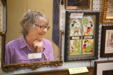 Ellen Krohn of Fortuna is reflected in a mirror at the annual Loleta Antique Show in the Loleta Fireman's Pavilion on Friday. The event, a fundraiser for the Loleta Volunteer Fire Department, continues today from 10 a.m. to 6 p.m. and Sunday from  10 a.m. to 4 p.m. (Shaun Walker -- The Times-Standard)