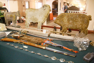 Metal weather vane animals, an otter pelt, and a contemporary .50 caliber rifle sit for sale at the booth of Humboldt Bay Trading Company of Richfield, Idaho. (Shaun Walker -- The Times-Standard)