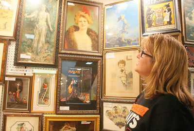 Ellen Cook of Windsor looks at framed prints at Wall Flowers Antique Prints' booth at the annual Loleta Antique Show in the Loleta Fireman's Pavilion on Friday. The event, a fundraiser for the Loleta Volunteer Fire Department, continues today from 10 a.m. to 6 p.m. and Sunday from  10 a.m. to 4 p.m. (Shaun Walker -- The Times-Standard)