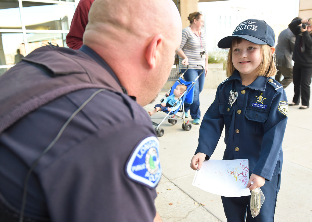 . Sidney Fahrenbruch, 4, meets with master police officer Dave Bonday Tuesday afternoon to donate money from her piggy bank to a Longmont police officer who has cancer. To view more photos and a video visit timescall.com. Lewis Geyer/Staff Photographer Oct. 24, 2017