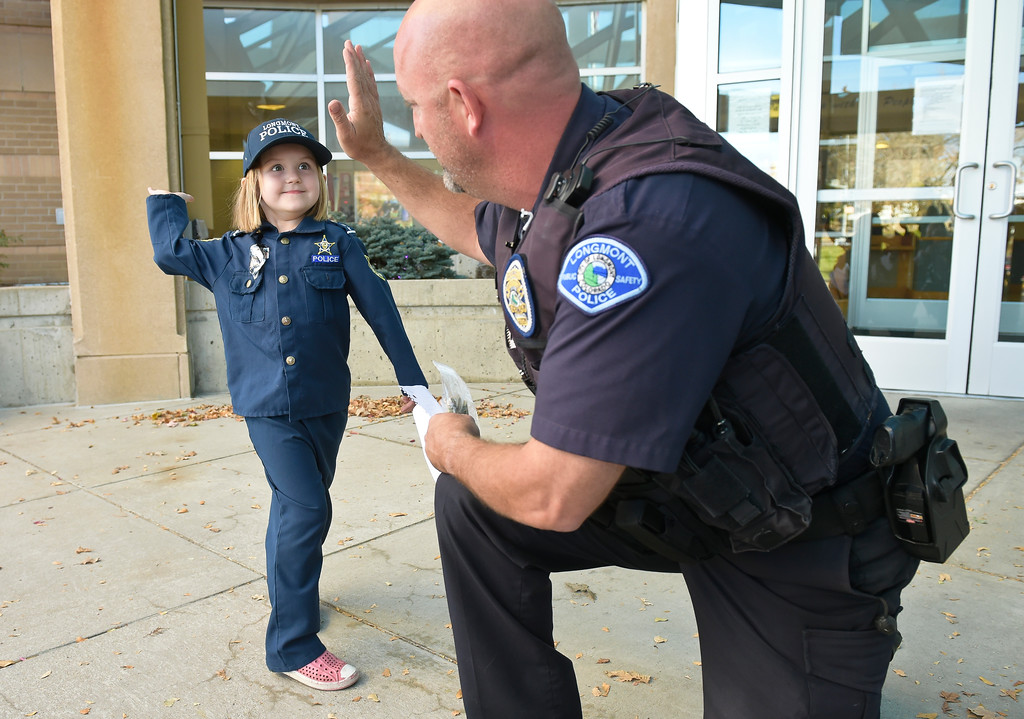 . Sidney Fahrenbruch, 4, gives a high five to master police officer Dave Bonday Tuesday afternoon after she donated money from her piggy bank to a Longmont police officer who has cancer. To view more photos and a video visit timescall.com. Lewis Geyer/Staff Photographer Oct. 24, 2017