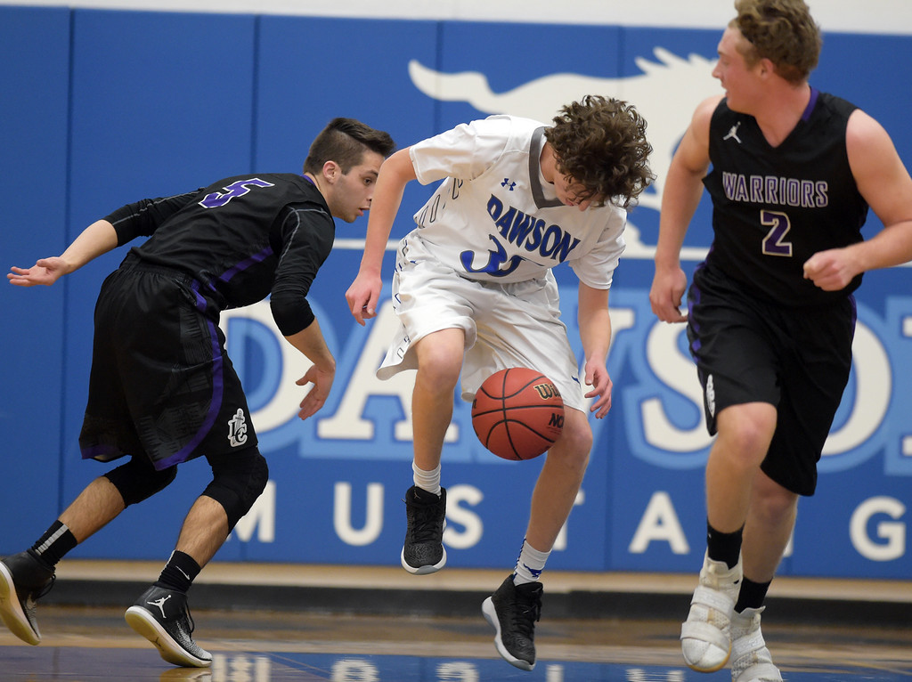 . The ball goes between the legs of Dawson\'s Gavyn Pure in the first quarter against Longmont Christian Thursday night at Alexander Dawson. To view more photos visit bocopreps.com. Lewis Geyer/Staff Photographer Feb. 16, 2017