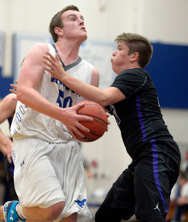 . Dawson\'s Nick Timms drives to the basket covered by Longmont Christian\'s Luke Puchino in the second quarter Thursday night at Alexander Dawson. To view more photos visit bocopreps.com. Lewis Geyer/Staff Photographer Feb. 16, 2017