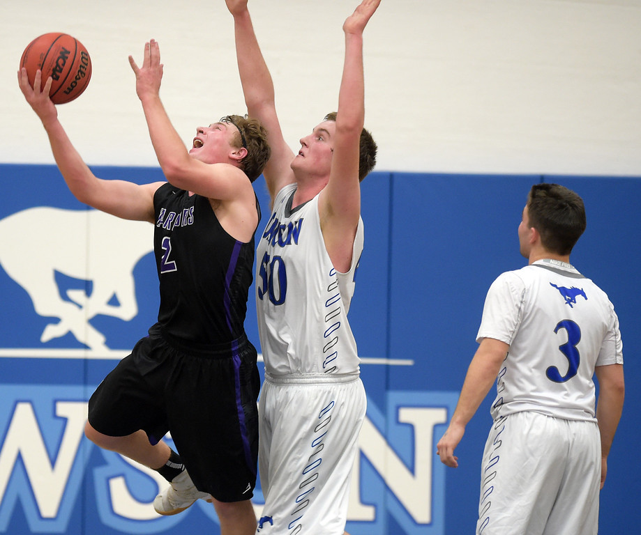 . Longmont Christian\'s Jackson Solem goes to the basket in front of Dawson\'s Nick Timms in the second quarter Thursday night at Alexander Dawson. To view more photos visit bocopreps.com. Lewis Geyer/Staff Photographer Feb. 16, 2017
