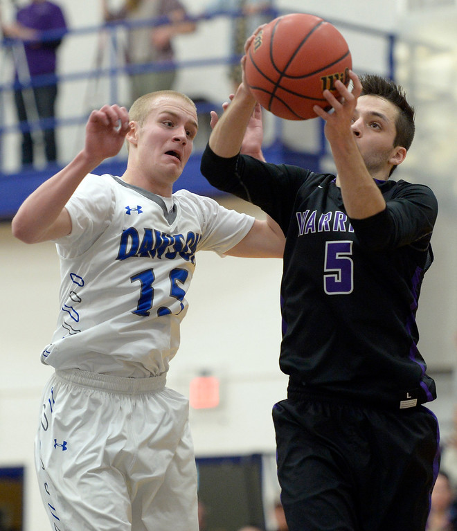 . Longmont Christian\'s Cameron Jauregui grabs a rebound in front of Dawson\'s Bryce Bickel in the second quarter Thursday night at Alexander Dawson. To view more photos visit bocopreps.com. Lewis Geyer/Staff Photographer Feb. 16, 2017