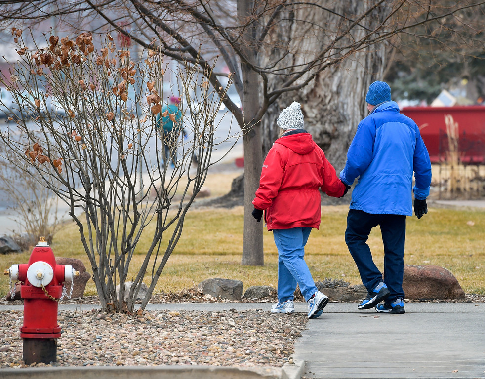 . Linda and Bob McLaughlin walk home after helping pick up litter in Collyer Park Friday morning. Lewis Geyer/Staff Photographer Feb. 09, 2018