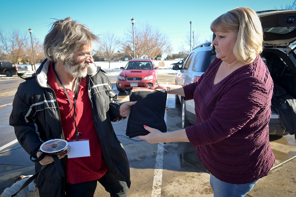 . Melissa Brim, of Longmont Helping Hands, hands a scarf and gloves to Leo Scott Monday afternoon. To view more photos and a video visit timescall.com. Lewis Geyer/Staff Photographer Jan. 22, 2018