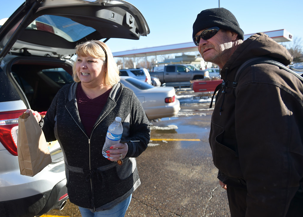 . Melissa Brim, of Longmont Helping Hands, distrubutes a sack lunch to Quint Gilman, right, and a friend in the Safeway parking along Ken Pratt Boulevard Monday afternoon. To view more photos and a video visit timescall.com. Lewis Geyer/Staff Photographer Jan. 22, 2018