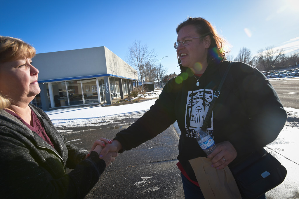 . Kindra Pierce, right, shakes hands with Melissa Brim, of Longmont Helping Hands, after receiving a sack lunch from Brim Monday afternoon. To view more photos and a video visit timescall.com. Lewis Geyer/Staff Photographer Jan. 22, 2018