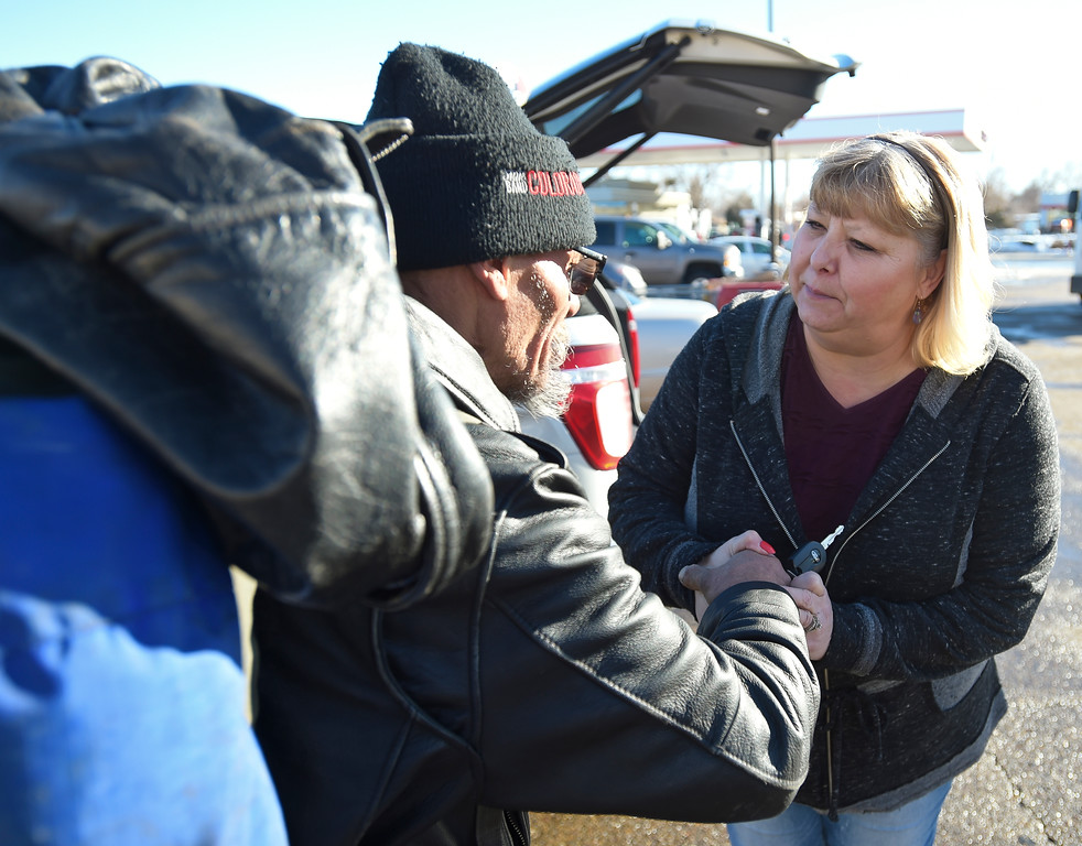 . Curtis Cramer shakes hands with Melissa Brim, of Longmont Helping Hands, after receiving a sack lunch from Brim in the Safeway parking lot along Ken Pratt Boulevard Monday afternoon. To view more photos and a video visit timescall.com. Lewis Geyer/Staff Photographer Jan. 22, 2018