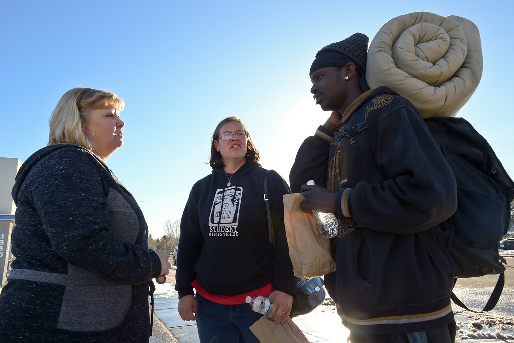 . Melissa Brim, of Longmont Helping Hands, hands out sack lunches to Charlie McConiughey and his wife Kindra Pierace Monday afternoon along Main Street near 15th Avenue. To view more photos and a video visit timescall.com. Lewis Geyer/Staff Photographer Jan. 22, 2018