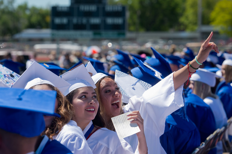 """Graduates Odalys Castorena (left) and Karina Hernandez-Mora acknowledge friends and family in the crowd during graduation at Longmont High School on Saturday.<br /> More photos:  <a href=""""http://www.dailycamera.com"""">http://www.dailycamera.com</a><br /> (Autumn Parry/Staff Photographer)<br /> May 28, 2016"""