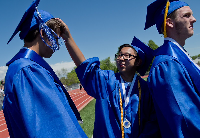 "Scott Murakami (center) fixes the cap of Brandon Julian (left) as they wait in line to graduate at Longmont High School.<br /> More photos:  <a href=""http://www.dailycamera.com"">http://www.dailycamera.com</a><br /> (Autumn Parry/Staff Photographer)<br /> May 28, 2016"