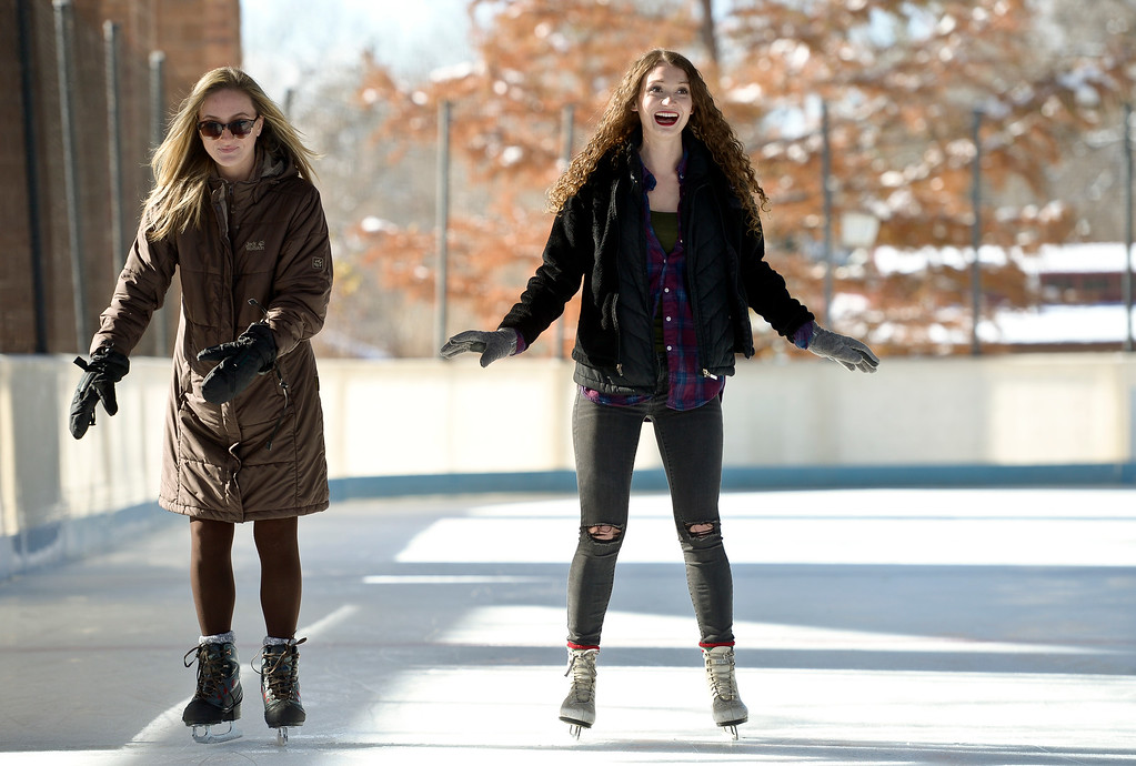 """. LONGMONT, CO - NOVEMBER 12: Sisters Elizabeth Lewis, left, and Kate Lewis are \""""hanging out\"""" together on the opening day of the season at the Longmont Ice Pavilion in Roosevelt Park Nov. 12, 2018. Kate said she came to Colorado from New York to visit Elizabeth who recently moved to the area.(Photo by Lewis Geyer/Staff Photographer)"""