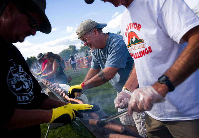 "Richard Showers helps cut a  450-foot-long bratwurst during the annual Longmont Oktoberfest at Roosevelt Park on Saturday. <br /> More photos:  <a href=""http://www.dailycamera.com"">http://www.dailycamera.com</a><br /> (Autumn Parry/Staff Photographer)<br /> September 24, 2016"
