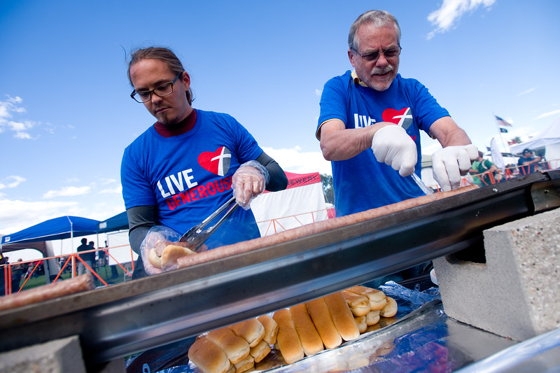 "Zach Klipstein (left) and his father Greg Klipstein help cut and serve a 450-foot-long bratwurst during the annual Longmont Oktoberfest at Roosevelt Park on Saturday. <br /> More photos:  <a href=""http://www.dailycamera.com"">http://www.dailycamera.com</a><br /> (Autumn Parry/Staff Photographer)<br /> September 24, 2016"
