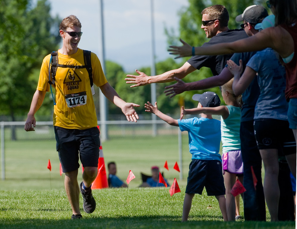 . David Harrold receives high fives as he nears the finish line during the Longmont Triathlon near Centennial Pool in Longmont on Sunday. More photos: www.dailycamera.com (Autumn Parry/Staff Photographer) June 5, 2016