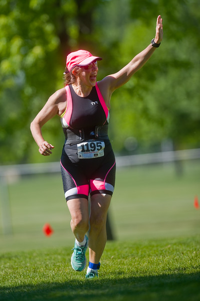"Anne Kelson waves to supporters as she nears the finish line during the during the Longmont Triathlon near Centennial Pool in Longmont on Sunday.<br /> More photos:  <a href=""http://www.dailycamera.com"">http://www.dailycamera.com</a><br /> (Autumn Parry/Staff Photographer)<br /> June 5, 2016"