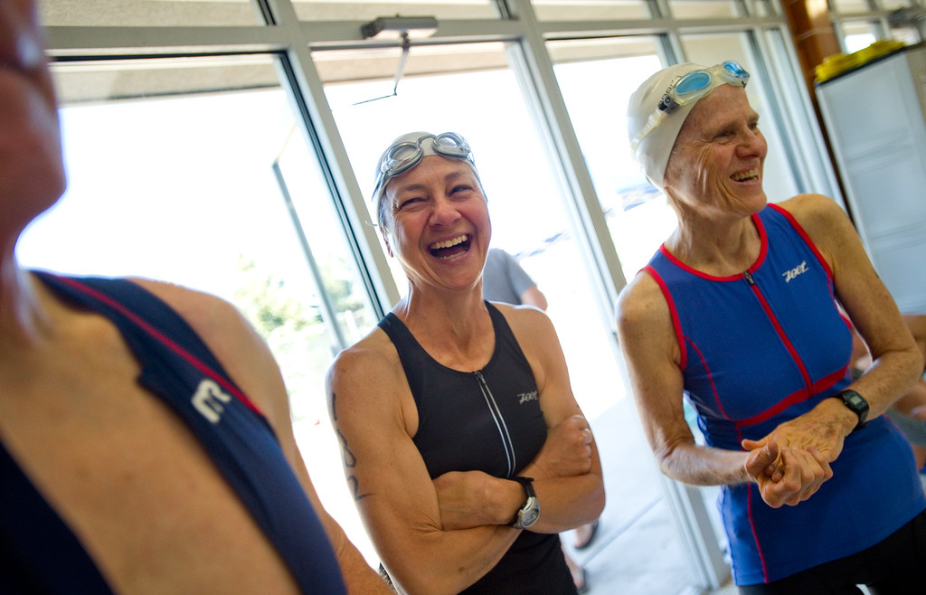. Ann Wilson (left) and Brooke Alt share a laugh while waiting to compete in the swimming portion of the Longmont Triathlon at Centennial Pool in Longmont on Sunday. More photos: www.dailycamera.com (Autumn Parry/Staff Photographer) June 5, 2016