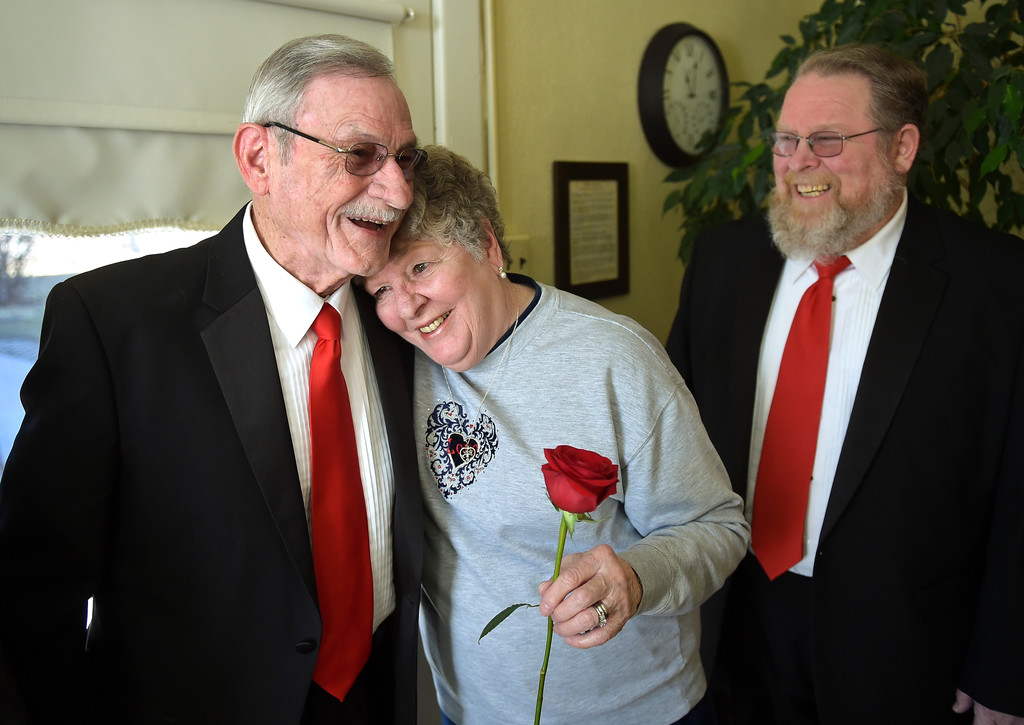 . Longs Peak Chorus member Davide Waddell gets a hug from his wife Maryann after Waddell, James Curts, right, and two other members of the chorus surprised Maryann with two Valentine\'s Day songs at the Callahan House Tuesday morning. The Waddells have been married for 55 years. To view a slideshow and video visit www.timescall.com. Lewis Geyer/Staff Photographer Feb. 14, 2017