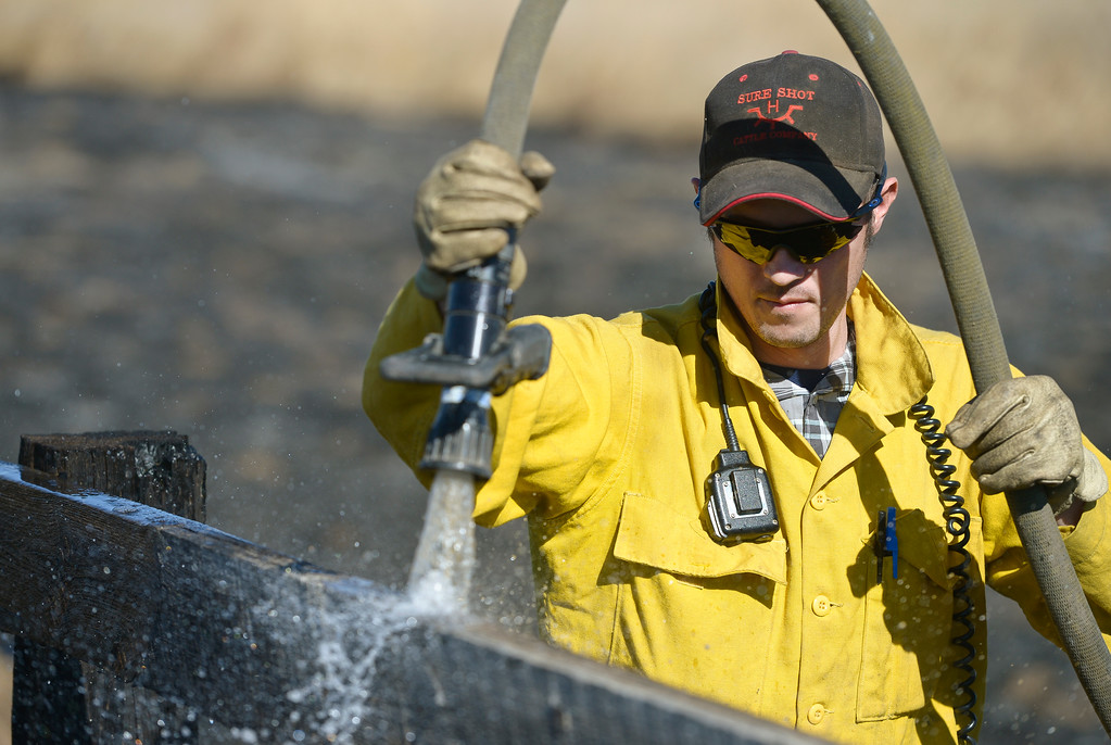 . Hygiene firefighter Cody Trevithick douses a fence at the scene 5-6 acre fire which started after a controlled burn got out of control Thursday morning in the 9000 block of Vermillion Road. Hygiene Fire was called at 11:18 a.m. and was assisted by Lyons Fire Department. To view a slideshow visit www.timescall.com. Lewis Geyer/Staff Photographer Feb. 16, 2017