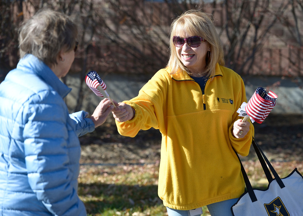 . LONGMONT, CO - NOVEMBER 10: Boulder County Veterans Service officer Karen Townsend hands out flags on Main Street before the start of the Longmont Veterans Day parade Nov. 10, 2018. (Photo by Lewis Geyer/Staff Photographer)