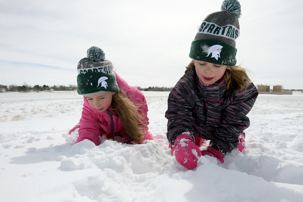 """. FIRESTONE, CO - MARCH 14: Sisters Gwyn, 9, left, and Adeline, 6, Halvorson play in the snow at Central Park March 14, 2019. \""""After yesterday I just couldn\'t keep them in anymore,\"""" said their father Brandon Halvorson. The pair attend Prairie Ridge Elementary.(Photo by Lewis Geyer/Staff Photographer)"""