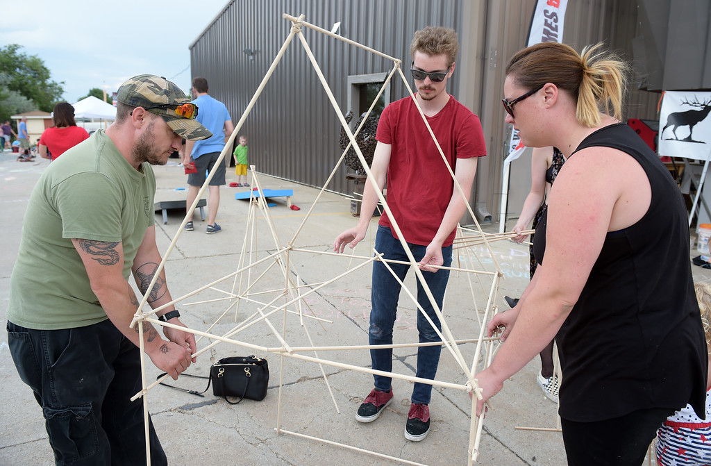 . From left: Kris Callier, Laird Mooney and his sister Alana Mooney build a structure with dowel rods and rubber bands at the TinkerMill\'s 4th of July Carnival Wednesday evening. To view more photos visit timescall.com. Lewis Geyer/Staff Photographer July 04, 2018