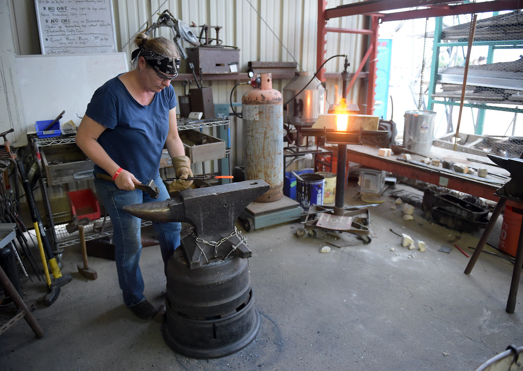 . Blacksmith Studio shop captain Kamber Sokulsky works on metal hooks during the TinkerMill\'s 4th of July Carnival Wednesday evening. To view more photos visit timescall.com. Lewis Geyer/Staff Photographer July 04, 2018