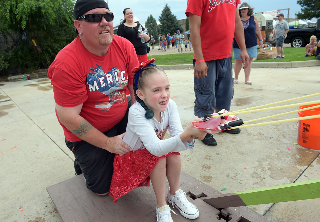 . Best Chris Howard holds onto his daughter Braelyn Howard, 9, while she uses a giant slingshot to shoot a water balloon across a parking lot at the TinkerMill\'s 4th of July Carnival Wednesday evening. To view more photos visit timescall.com. Lewis Geyer/Staff Photographer July 04, 2018