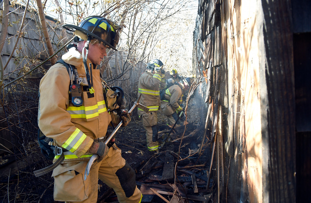 . LONGMONT, CO - NOVEMBER 6: Longmont firefighters remove charred siding from a multi-car garage after a fire broke between two garage buildings at the rear of 1611 Warren Ave., Nov. 6, 2018. (Photo by Lewis Geyer/Staff Photographer)