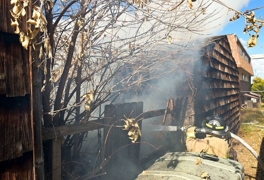 . LONGMONT, CO - NOVEMBER 6: Station 2 firefighter/paramedic Tony Priola extinguishes a fire between two multi-car garages behind the apartment building at 1611 Warren Ave., Nov. 6, 2018. (Photo by Lewis Geyer/Staff Photographer)